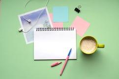 Tableta con una aguja en un fondo verde Una taza de café, auriculares, foto foto de archivo libre de regalías