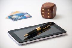 Tableta con una pluma negra, dados de madera y tarjetas de crédito en el CCB Fotos de archivo