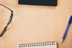 Tableta con vidrios del negro de la pantalla en blanco y una libreta en la tabla de madera de la oficina, Imagen de archivo libre de regalías