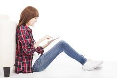 Tableta conmovedora de la mujer joven y el sentarse en el piso Fotos de archivo libres de regalías