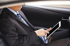 Tableta conmovedora del hombre de negocios en el coche imagen de archivo