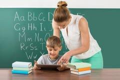 Tableta de With Boy Using Digital del profesor en sala de clase imagenes de archivo