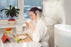 Tableta de consumición de la lectura del té de la mujer en el humectador Imágenes de archivo libres de regalías