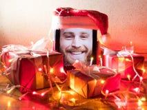 Tableta de Digitaces con el varón barbudo en la pantalla con cualidades de la Navidad alrededor Foto de archivo libre de regalías