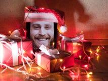 Tableta de Digitaces con el varón barbudo en la pantalla con los regalos y las luces de la Navidad alrededor Imagen de archivo