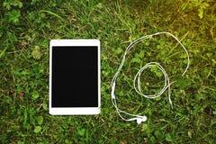 Tableta de Digitaces con la pantalla en blanco y el auricular foto de archivo
