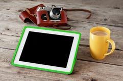 Tableta de Digitaces con la pantalla negra con la cámara del café y del vintage en el primer de madera del fondo Imagen de archivo libre de regalías