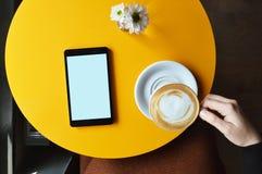 Tableta de Digitaces encima de la tabla del café y de una taza de la tenencia de la mano de la mujer de café imagen de archivo