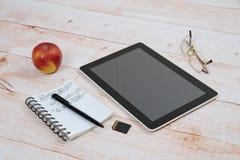 Tableta de Digitaces, libreta, pluma, vidrios en una tabla Fotos de archivo libres de regalías