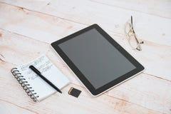 Tableta de Digitaces, libreta, pluma, vidrios en una tabla Imagen de archivo libre de regalías