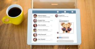 Tableta de Digitaces que exhibe medios sitio web social por la taza de café en la tabla Foto de archivo