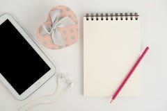 Tableta de la caja de regalo del corazón y cuaderno en el fondo blanco Imágenes de archivo libres de regalías