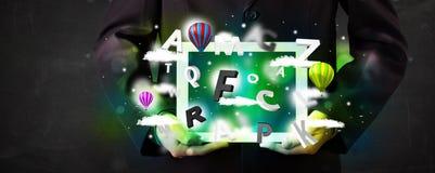 Tableta de la demostración de la persona joven con las letras y el cielo abstractos Imagen de archivo