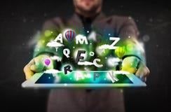 Tableta de la demostración de la persona joven con las letras y el cielo abstractos Imagen de archivo libre de regalías