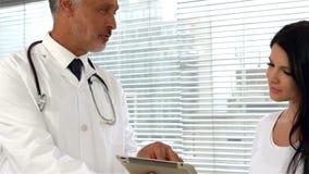 Tableta de la demostración del doctor al paciente embarazada metrajes