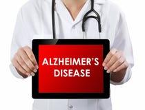Tableta de la demostración del doctor con el texto de la ENFERMEDAD DE ALZHEIMER imagen de archivo