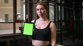Tableta de la demostración de la deportista con la pantalla del verde del chromakey en la cámara que es tranquila y concentrada e almacen de video