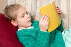 Tableta de la lectura de la chica joven en el sofá Fotografía de archivo libre de regalías