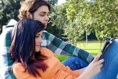 Tableta de la lectura de los pares en parque Imágenes de archivo libres de regalías