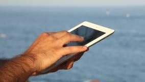 Tableta de la ojeada al lado de la costa panorámica almacen de video