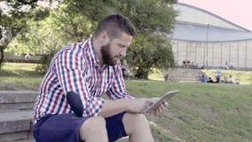 Tableta de la ojeada del hombre joven, sentándose en las escaleras tiro del resbalador almacen de metraje de vídeo