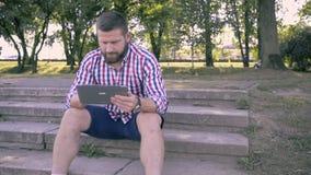 Tableta de la ojeada del hombre joven, sentándose en las escaleras Tiro del resbalador y de la cacerola almacen de metraje de vídeo