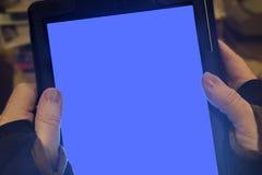 Tableta de la pantalla en blanco sostenida en manos Foto de archivo