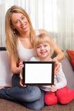 Tableta de la tenencia de la madre y de la hija con la pantalla en blanco Fotos de archivo