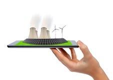 Tableta de la tenencia de la mano con las turbinas de un viento, el panel solar y la central nuclear Imágenes de archivo libres de regalías