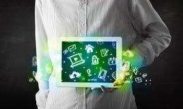 Tableta de la tenencia de la persona con los medios iconos y símbolos verdes Fotos de archivo