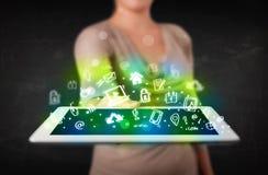 Tableta de la tenencia de la persona con los medios iconos y símbolos verdes Foto de archivo