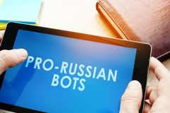 Tableta de la tenencia del hombre con los bots favorable-rusos Concepto ruso de la propaganda de Internet foto de archivo libre de regalías