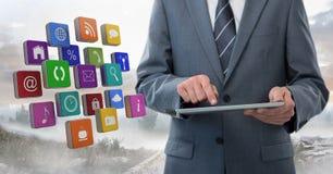 Tableta de la tenencia del hombre de negocios con los iconos de los apps afuera en paisaje Foto de archivo libre de regalías