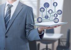 Tableta de la tenencia del hombre de negocios con los iconos de los apps en oficina Fotografía de archivo