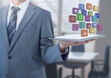 Tableta de la tenencia del hombre de negocios con los iconos de los apps en oficina Foto de archivo
