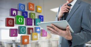 Tableta de la tenencia del hombre de negocios con los iconos de los apps en oficina de la fábrica del taller Imagenes de archivo