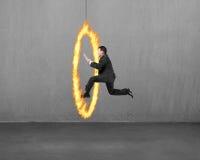 Tableta de la tenencia del hombre de negocios que salta a través de aro del fuego con el concre Imagen de archivo libre de regalías
