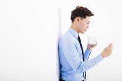 tableta de la tenencia del hombre de negocios y el inclinarse contra la pared blanca Imagen de archivo