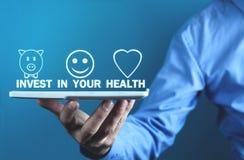 Tableta de la tenencia del hombre Invierta en su salud fotos de archivo