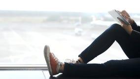 Tableta de la tenencia de la mujer joven en manos y el sentarse en aeropuerto metrajes