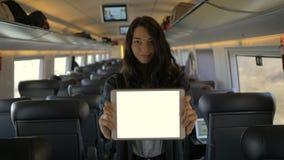 Tableta de la tenencia de la mujer joven mientras que viaja en tren metrajes