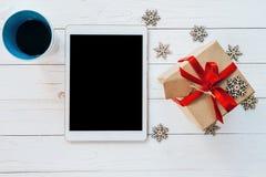 Tableta de la visión superior, café de la taza, y caja de regalo con los copos de nieve en whi Imágenes de archivo libres de regalías