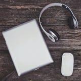 Tableta de la visión superior con los auriculares y el ratón en un fondo de madera Imágenes de archivo libres de regalías