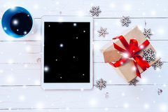 Tableta de la visión superior, taza de café y caja de regalo con nieve y el copo de nieve Foto de archivo