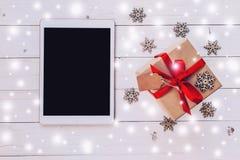 Tableta de la visión superior, y caja de regalo con la nieve, copos de nieve en blanco Imagenes de archivo
