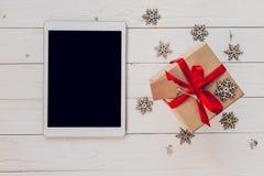 Tableta de la visión superior, y caja de regalo con los copos de nieve en la parte posterior blanca de madera Imágenes de archivo libres de regalías