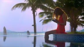 Tableta de las aplicaciones de la muchacha que se sienta en el borde de la piscina contra el primer de las palmas almacen de metraje de vídeo
