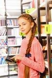 Tableta de los controles de la muchacha cerca del estante en biblioteca Imágenes de archivo libres de regalías
