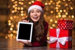 Tableta de mentira y que muestra femenina joven rizada alegre pantalla en blanco Fotografía de archivo libre de regalías