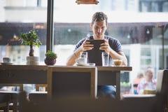 Tableta de observación del hombre joven en café Foto de archivo libre de regalías